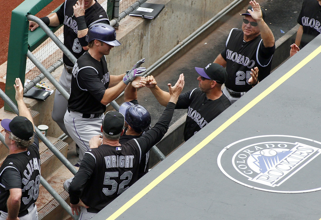 . Josh Rutledge #14 of the Colorado Rockies celebrates with teammates after hitting a two-run home run in the first inning against the Pittsburgh Pirates during the game at PNC Park on July 20, 2014 in Pittsburgh, Pennsylvania.  (Photo by Justin K. Aller/Getty Images)