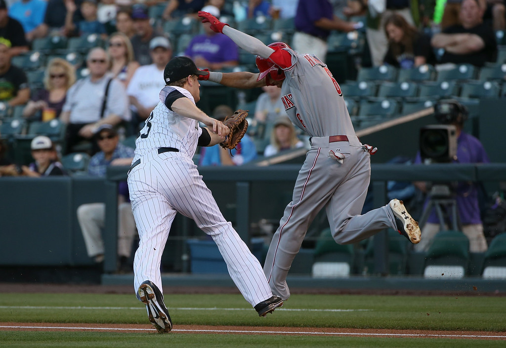 . DENVER, CO - AUGUST 14:  Billy Hamilton #6 of the Cincinnati Reds grounds out bunting to first baseman Justin Morneau #33 of the Colorado Rockies in the first inning at Coors Field on August 14, 2014 in Denver, Colorado.  (Photo by Doug Pensinger/Getty Images)