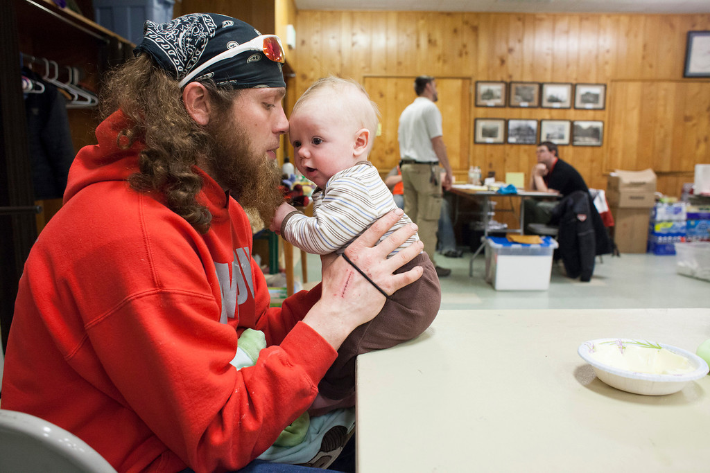 . Kristopher Langton shares a moment with his son, Kristian Langton (5 months), at a temporary Red Cross shelter at the Darrington Community Center in Darrington, Washington on Sunday, March 23, 2014. A massive mudslide in Oso, Washington killed at least eight and left many missing, and Kristopher Langton was one of the first to arrive and offer aid. Against the wishes of authorities, Langton says he traveled more than a mile across the entire mudslide, wading through debris and mud that resembled quicksand to help rescue four adults and an infant. (Photo by David Ryder/Getty Images)