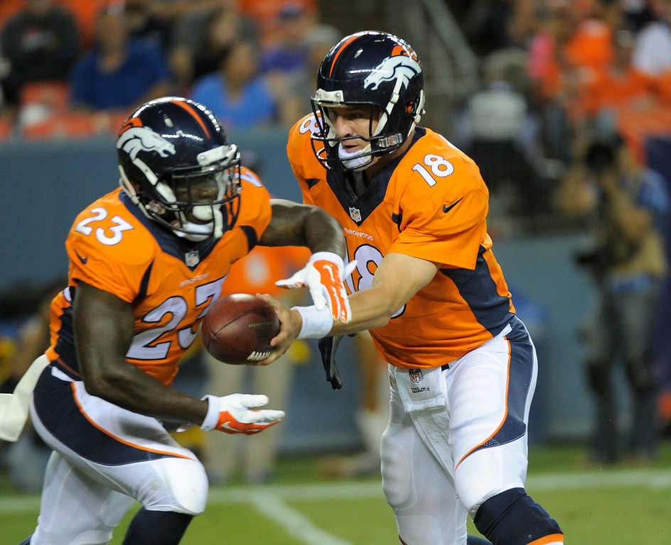 . DENVER, CO - AUGUST 23: Denver Broncos quarterback Peyton Manning (18) hands off to Denver Broncos running back Ronnie Hillman (23) during the second quarter against the Houston Texans August 23, 2014 at Sports Authority Field at Mile High Stadium. (Photo by John Leyba/The Denver Post)