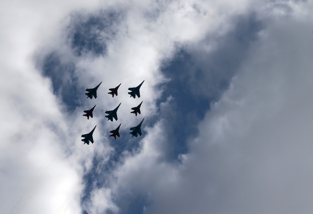 ". Russian pilot group the ""Russian Knights\"" along with the \""Strizhi\"" group perform at the opening of the MAKS Air Show in Zhukovsky outside Moscow on Tuesday, Aug. 27, 2013. (AP Photo/Ivan Sekretarev)"