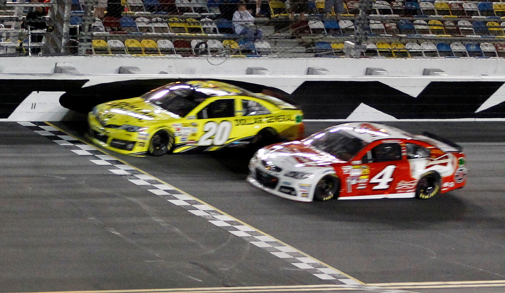 . Matt Kenseth (20) races to the finish ahead of Kevin Harvick (4) to win the first of two NASCAR Sprint Cup series qualifying auto races at Daytona International Speedway in Daytona Beach, Fla., Thursday, Feb. 20, 2014. (AP Photo/Terry Renna)