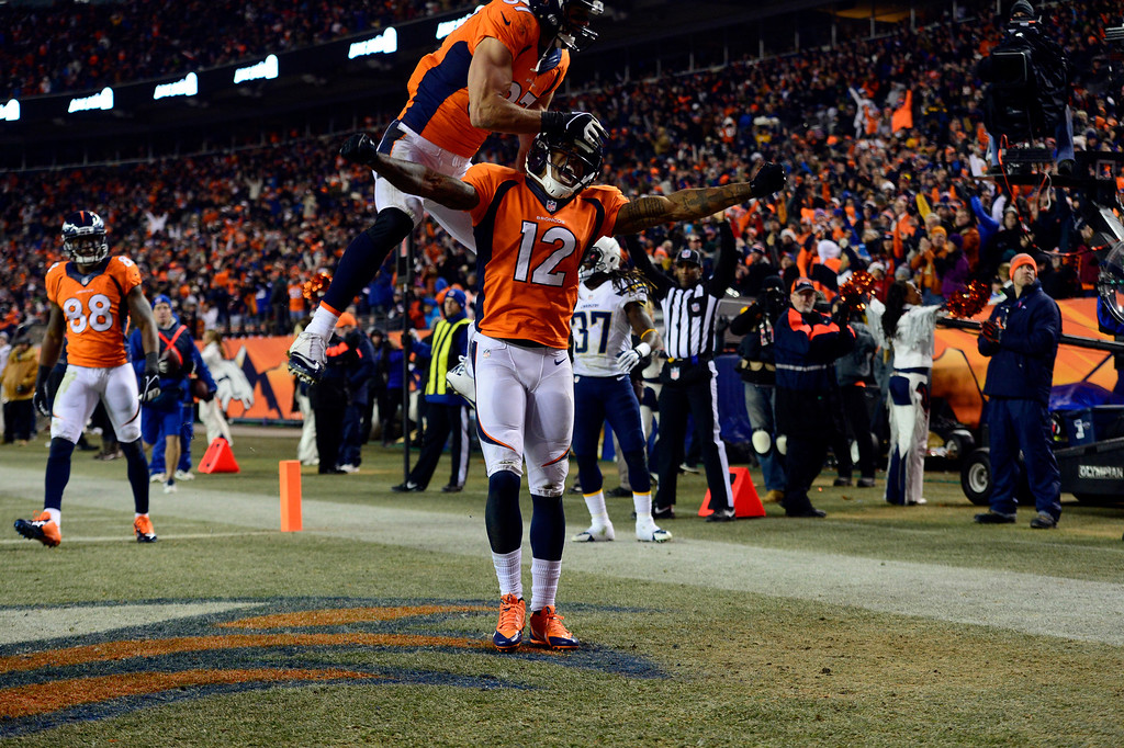. Denver Broncos wide receiver Andre Caldwell (12) celebrates with Denver Broncos wide receiver Eric Decker (87) in the end zone  after scoring a touchdown in the second half.  This touchdown brought the score to Chargers 24 and Broncos 17.  The Denver Broncos vs. the San Diego Chargers at Sports Authority Field at Mile High in Denver on December 12, 2013. (Photo by AAron Ontiveroz/The Denver Post)