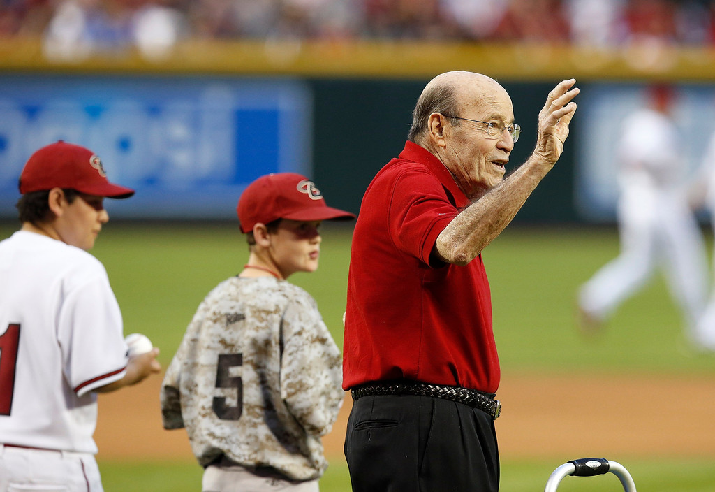 . Former Arizona Diamondbacks announcer and MLB player, Joe Garagiola, Sr., right, waves to the crowd as he is introduced along with local little league players for the first pitch ceremonies prior to an opening day baseball game, Monday, March 31, 2014, in Phoenix. (AP Photo/Ross D. Franklin)