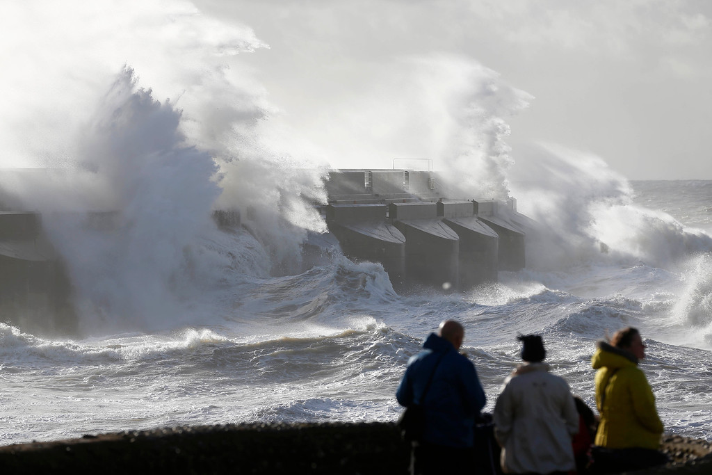 . People watch the waves batter into the sea wall of a marina in Brighton, south England, Monday, Oct. 28, 2013. A major storm with hurricane force winds is lashing much of Britain, causing flooding and travel delays including the cancellation of roughly 130 flights at London\'s Heathrow Airport. Weather forecasters say it is one of the worst storms to hit Britain in years. (AP Photo/Sang Tan)