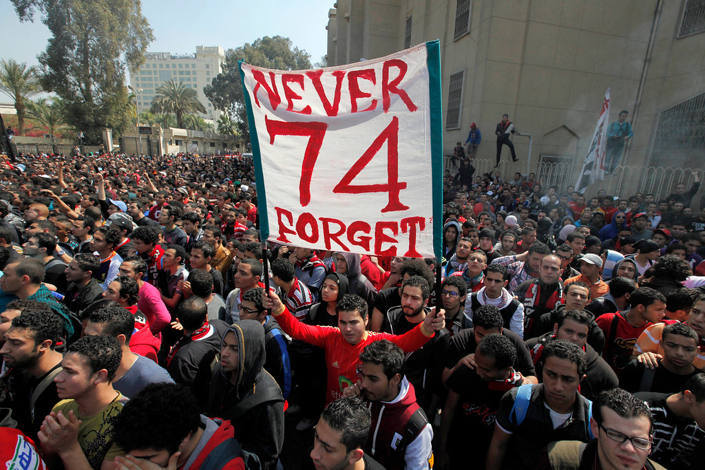 . An Egyptian soccer fan of Al-Ahly club raises a banner honoring fellow fans killed in a 2012 stadium riot in the club headquarters in Cairo, Egypt, Saturday, March 9, 2013. (AP Photo/Amr Nabil)