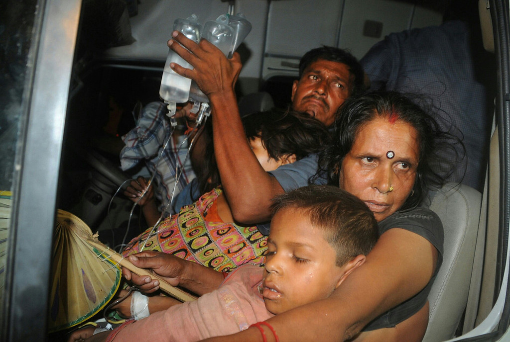 . An Indian family, with their son who fell ill after consuming a free school meal, are transported outside the Patna Medical College Hospital in Patna.  Twenty-one children have died after eating a free lunch feared to contain poisonous chemicals at a school in eastern India, officials said July 17, 2013 sparking angry protests as mobs ran riot.   AFP PHOTOSTR/AFP/Getty Images