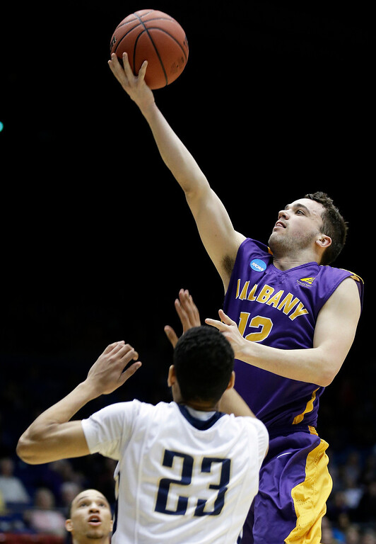. Albany guard Peter Hooley (12) drives against Mount St. Mary\'s guard Julian Norfleet (23) during the first half of a first-round game of the NCAA college basketball tournament, Tuesday, March 18, 2014, in Dayton, Ohio. (AP Photo/Al Behrman)