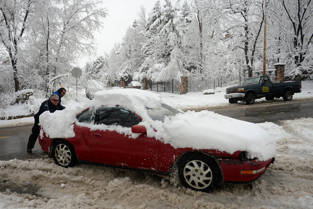 . BOULDER, CO. - APRIL 23: Boulder Police officer Steven Cast pushing a motorist stuck in the deep  snow and ice on 14th Ave in April 23, 2013 Boulder, Colorado. (Photo By Joe Amon/The Denver Post)