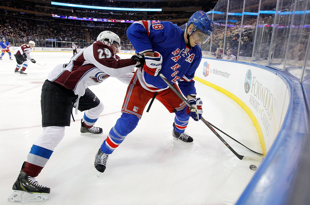 . Marc Staal #18 of the New York Rangers keeps the puck from Nathan MacKinnon #29 of the Colorado Avalanche during a game at Madison Square Garden on February 4, 2014 in New York City.  (Photo by Jim McIsaac/Getty Images)