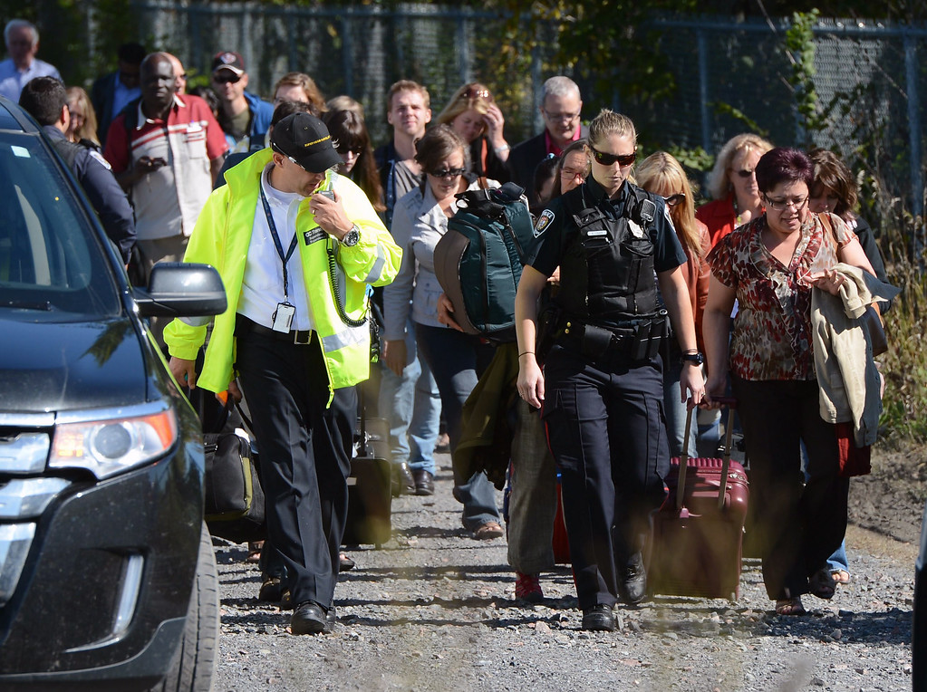 . Train passengers are escorted away from the scene following a collision with a city bus at a crossing in Ottawa, Ontario, Wednesday, Sept. 18, 2013. An Ottawa Fire spokesman said there are ìmultiple fatalitiesî and a number of people injured from the bus, but no injuries reported from the train. (AP Photo/The Canadian Press, Sean Kilpatrick)