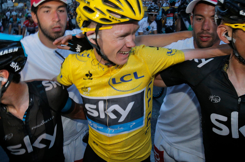 . Tour de France 2013 winner Christopher Froome of Britain, wearing the overall leader\'s yellow jersey, hugs teammates after the 21st and last stage of the 100th edition of the Tour de France cycling race over 133.5 kilometers (83.4 miles) with start in Versailles and finish in Paris, France, Sunday July 21 2013.  (AP Photo/Christophe Ena)
