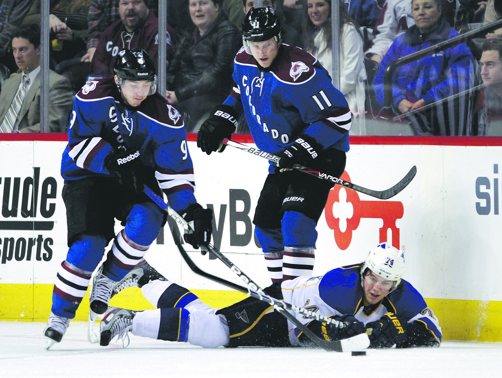 . Colorado Avalanche center Matt Duchene (9) carries the puck away from St. Louis Blues right wing T.J. Oshie (74) as Avalanche left wing Jamie McGinn (11) watches during the first period of an NHL hockey game, Wednesday, Feb. 20, 2013, in Denver. (AP Photo/Joe Mahoney)