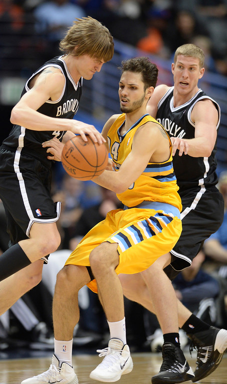 . DENVER, CO. - FEBRUARY 27, 2014: Denver guard Evan Fournier got squeezed between Andrei Kirilenko, left, and Mason Plumlee, right, in the first half. The Denver Nuggets hosted the Brooklyn Nets at the Pepsi Center Thursday night, February 27, 2014. Photo By Karl Gehring/The Denver Post