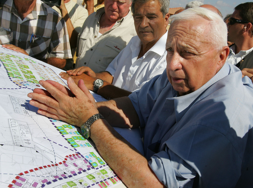 . Israeli Prime Minister Ariel Sharon (R) leans over housing plans as he meets with contractors who are building temporary housing for settlers due to be evacuated from the Gaza Strip under his disengagement plan July 5, 2005 at the Nitzanim construction site in southern Israel. Earlier in the day, Sharon reiterated that Israel will react with extremely harsh measures to Palestinian attacks during the pullout from the Gaza Strip. (Photo by David Silverman/Getty Images)