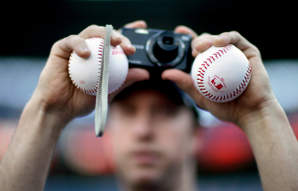 . Jonathan Buehler, of Alpharetta, Ga., holds two baseballs while taking a picture before the start of an opening day baseball game between the Atlanta Braves and the Philadelphia Phillies, Monday, April 1, 2013, in Atlanta. (AP Photo/David Goldman)