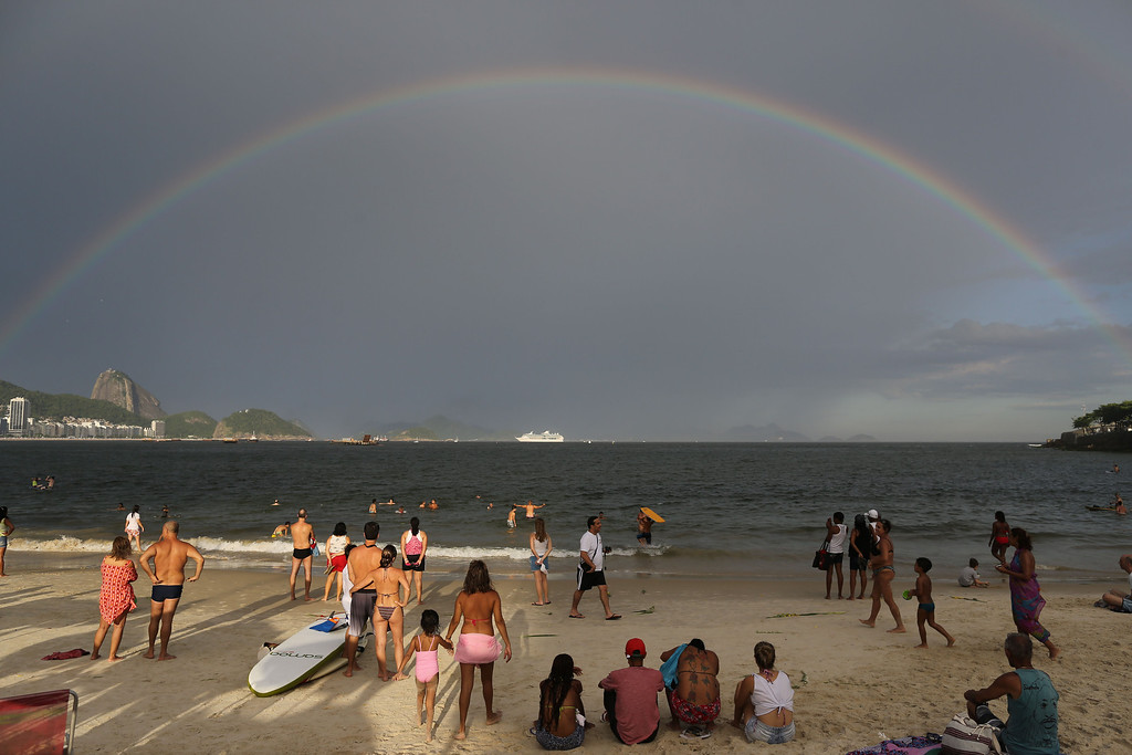 . A rainbow arches across the horizon during New Year\'s Eve festivities on Copacabana beach in Rio de Janeiro, Brazil, Tuesday, Dec. 31, 2013. Sugar Loaf is pictured on left. (AP Photo/Leo Correa)