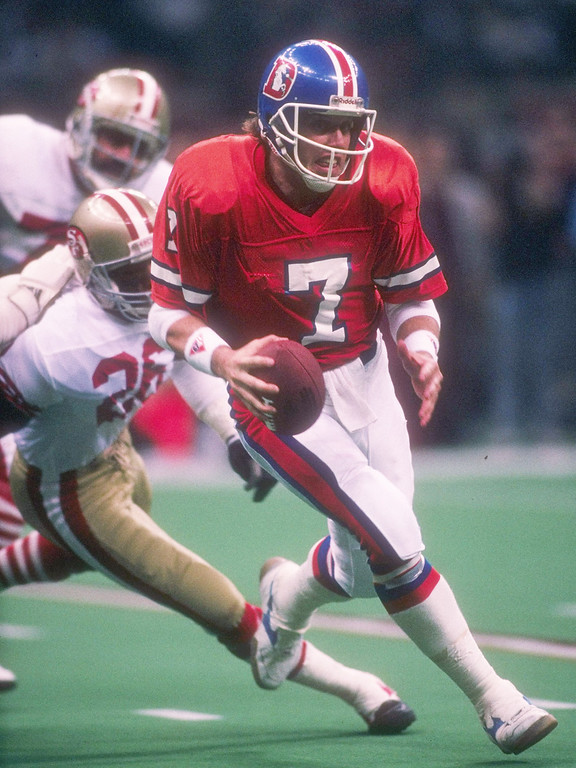 . 28 Jan 1990: Quarterback John Elway of the Denver Broncos runs with the ball as a pair of San Francisco 49ers players chase him during Super Bowl XXIV at the Louisiana Superdome in New Orleans, Louisiana. The 49ers won the game, 55-10.