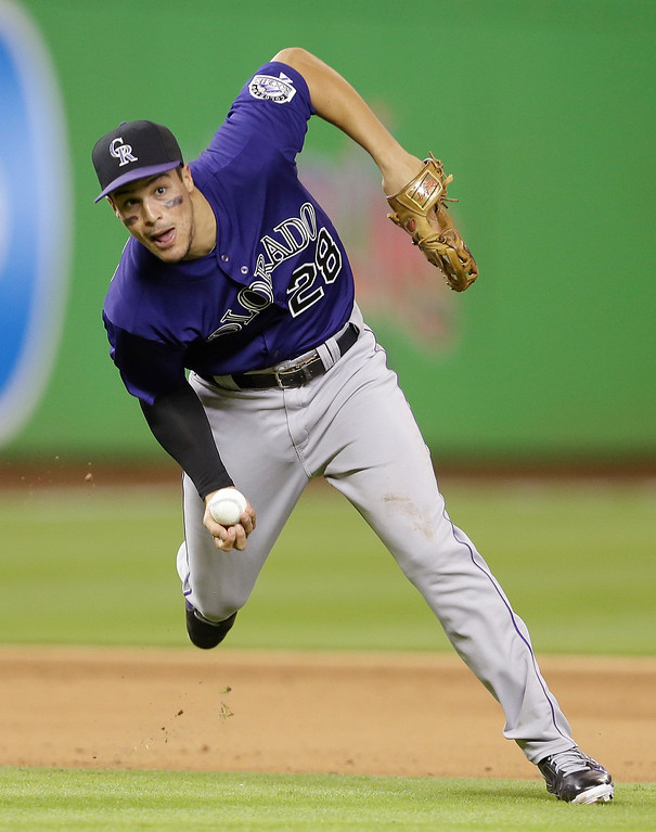 . Colorado Rockies third baseman Nolan Arenado throws  late to first base in the fifth inning during the inning of an opening day baseball game, Monday, March 31, 2014, in Miami. (AP Photo/Lynne Sladky)