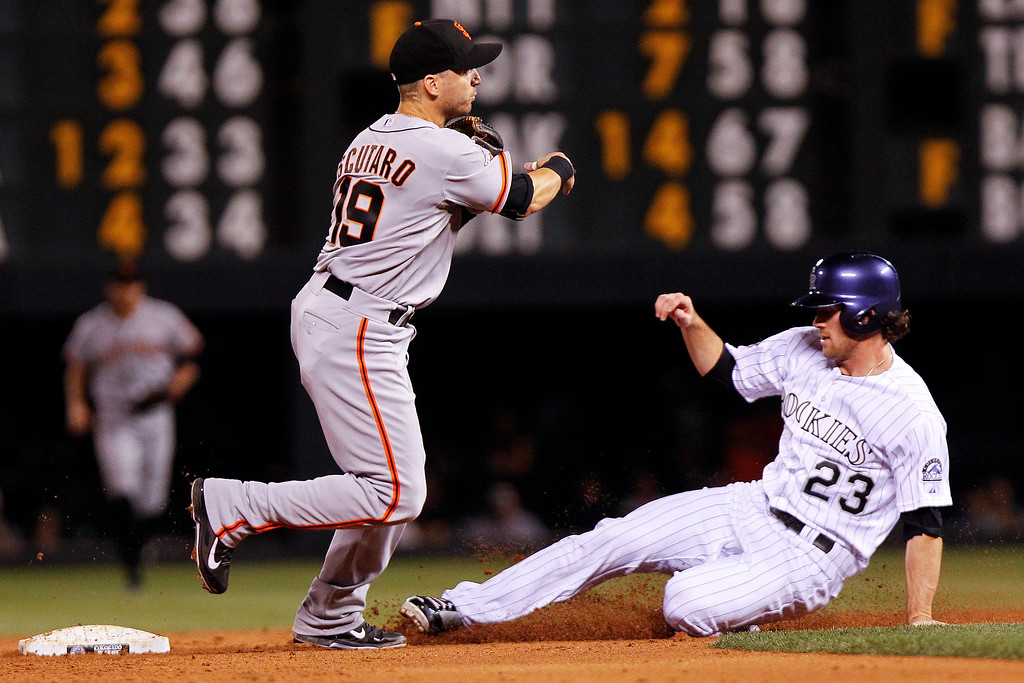 . San Francisco Giants\' Marco Scutaro, left, throws over Colorado Rockies\' Charlie Culberson but misses on the double play with Jhoulys Chacin reaching first during the sixth inning of a baseball game, Wednesday, Aug. 28, 2013, in Denver. (AP Photo/Barry Gutierrez)