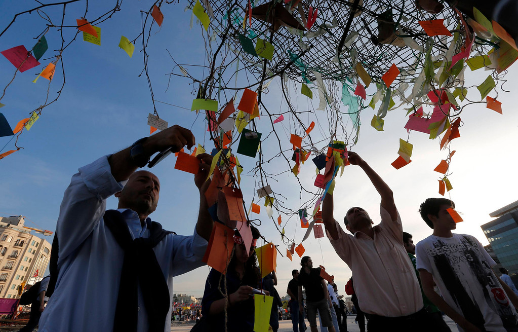 . People place notes bearing their messages on a tree at Taksim Square in Istanbul June 6, 2013. Turkish Prime Minister Tayyip Erdogan denounced those behind a week of violent demonstrations on Thursday, causing a sell-off on the Turkish stock exchange from investors worried that his defiant rhetoric will further enflame public wrath.  REUTERS/Osman Orsal