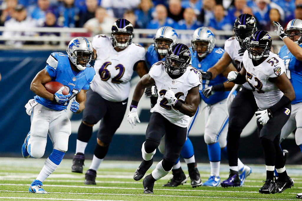 . Detroit Lions running back Reggie Bush, left, pulls away from the Baltimore Ravens defense during the first quarter of an NFL football game in Detroit, Monday, Dec. 16, 2013. (AP Photo/Rick Osentoski)
