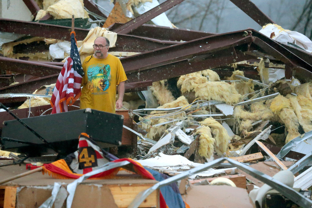 . Benjamin Pierce, a patron of the Botkinburg Foursquare church, sifts through the wreckage of the church on Wednesday, April 10, 2013 after a storm demolished it just north of Clinton, Ark. The National Weather Service is surveying areas Thursday to determine whether tornadoes or strong winds caused damage.  (AP Photo/The Log Cabin Democrat, Eric White)
