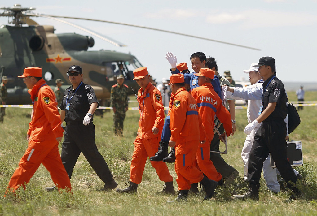 . Chinese astronaut Nie Haisheng (4th R) waves after he gets out of the Shenzhou-10 spacecraft that landed on the grasslands of north China\'s Inner Mongolia region on June 26, 2013, after a 15-day mission in space. China completed its longest manned space mission on June 26 as its Shenzhou-10 spacecraft and three crew members safely returned to Earth, in a major step towards Beijing\'s goal of building a permanent space station by 2020.  AFP PHOTOSTR/AFP/Getty Images