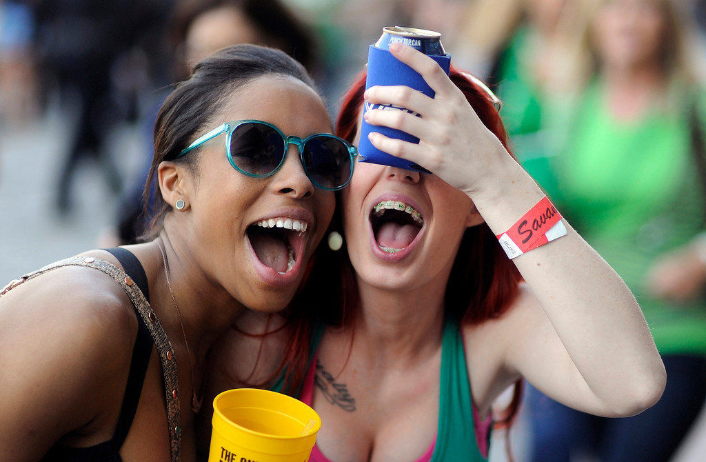 . Rachel Everett, right, and her friend Bianca Lee try to catch a marshmellow in their mouths while during the 189-year-old St. Patrick\'s Day celebration on River Street, Friday, March 15, 2013, in Savannah, Ga. (AP Photo/Stephen Morton)