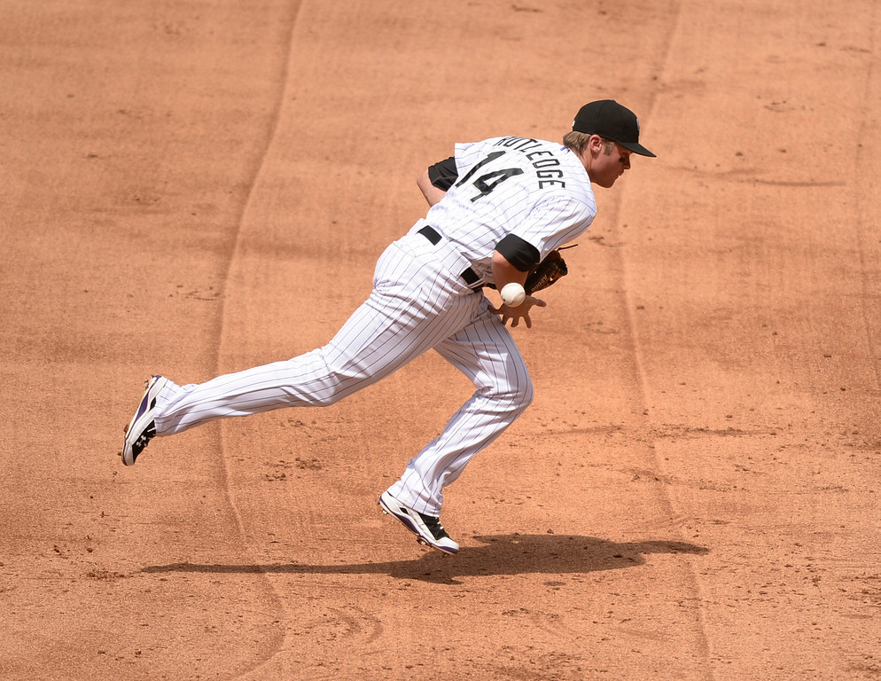 . DENVER, CO - JUNE 20: Colorado infielder Josh Rutledge muffed a ball hit to him by Brewers\' batter Khris Davis. Rutledge then threw high to first base and Davis went to second. The Colorado Rockies hosted the Milwaukee Brewers at Coors Field Saturday afternoon, June 21, 2014. Photo by Karl Gehring/The Denver Post