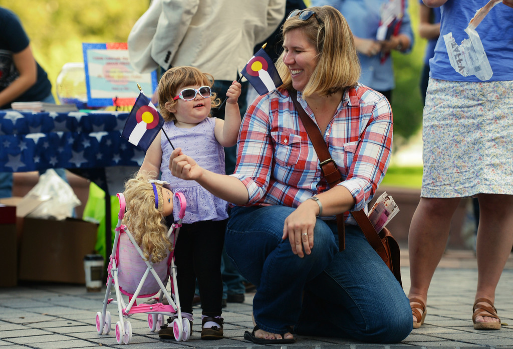 . Greta Vanderberg-Reynolds, 2, and her mother Erin Vanderberg wave small Colorado flags during a celebration, for the 138th anniversary of the state of Colorado, on the west steps of Colorado State Capitol in Denver, August 01, 2014. The celebration included dancing, a cake, a performance from the Colorado Army National Guard Band, and more. (Photo by RJ Sangosti/The Denver Post)