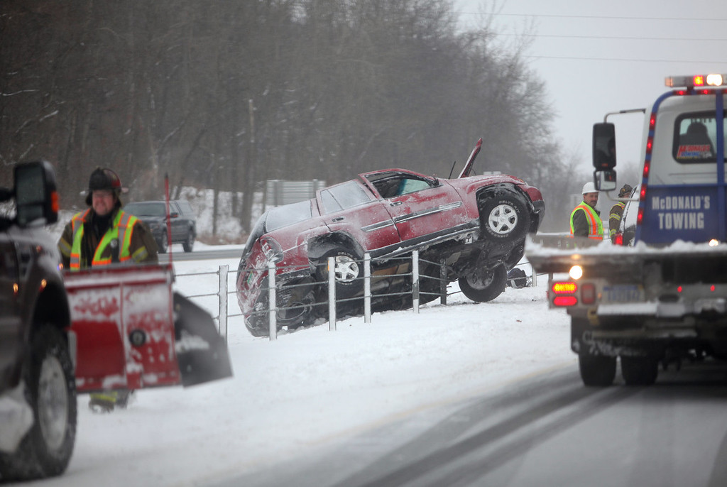 . Emergency workers respond to a vehicle that slid off the road on Interstate 94  in Texas Township near Kalamazoo, Mich. A multi-day storm dropped up to a foot of snow on parts of Michigan, causing crashes and spinouts on roadways. Snowfall began Tuesday and continued Thursday morning.  (AP Photo/Kalamazoo Gazette-MLive Media Group, Mark Bugnaski)
