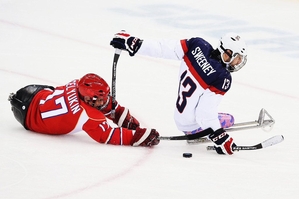 . Joshua Sweeney of the USA makes a break past Vadim Selyukin of Russia during the ice sledge hockey gold medal game between the Russian Federation and the United States of America at the Shayba Arena during day eight of the 2014 Paralympic Winter Games on March 15, 2014 in Sochi, Russia.  (Photo by Hannah Peters/Getty Images)