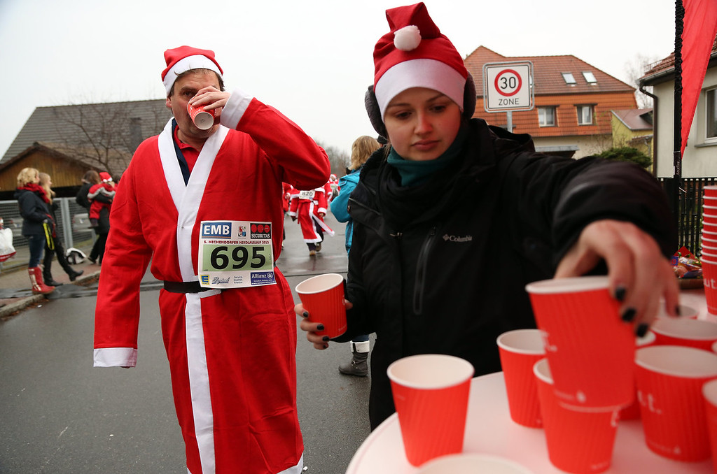 . A participant takes a cup of hot punch while competing in the 5th annual Michendorf Santa Run (Michendorfer Nikolauslauf) on December 8, 2013 in Michendorf, Germany. Over 900 people took part in this year\'s races, which included one for children and one for adults.  (Photo by Adam Berry/Getty Images)