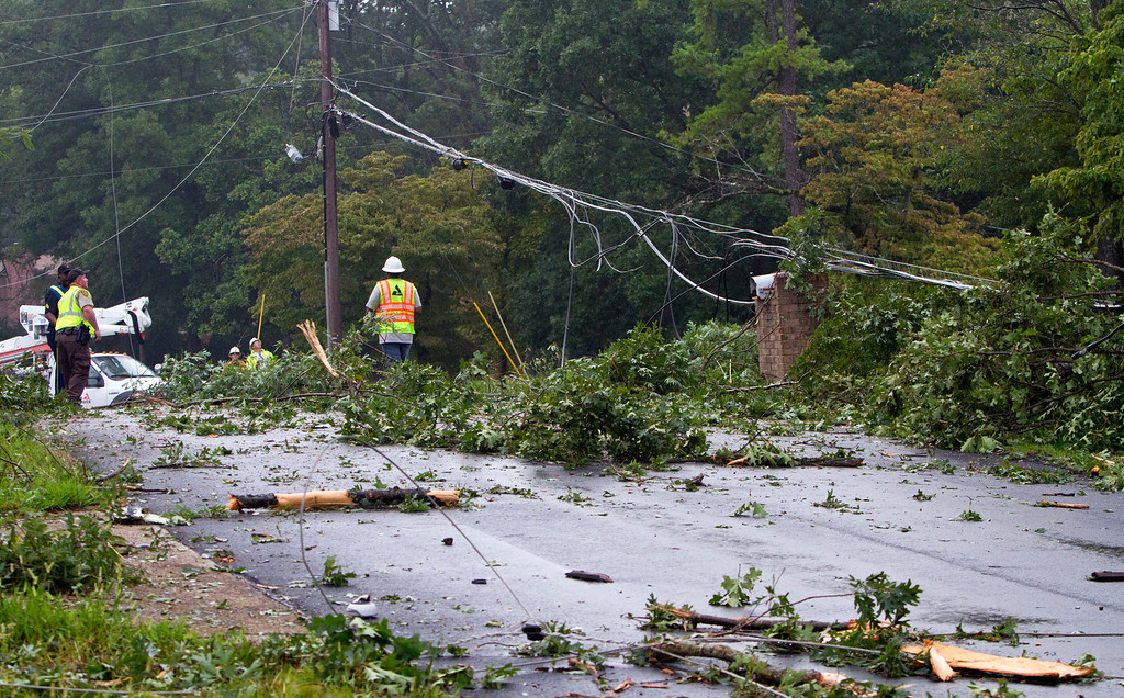 . Fire crews assess damage on a street where a UPS cargo plane knocked down trees and power lines as it crashed at the Birmingham-Shuttlesworth International Airport in Birmingham, Ala., on Wednesday, Aug. 14, 2013. (AP Photo/Butch Dill)