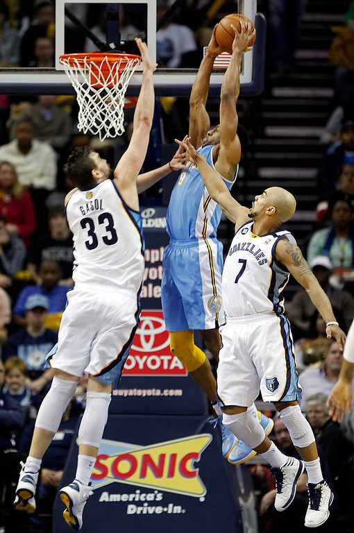 . Denver Nuggets guard Andre Iguodala (9) goes to the basket against Memphis Grizzlies center Marc Gasol (33), of Spain, and guard Jerryd Bayless (7) in the second half of an NBA basketball game on Saturday, Dec. 29, 2012, in Memphis, Tenn. The Grizzlies won 81-72. (AP Photo/Lance Murphey)