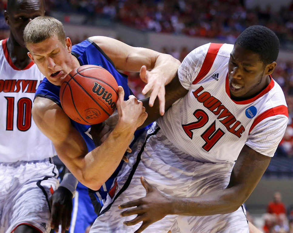 . Duke Blue Devils forward Mason Plumlee (5) fights for a loose ball with Louisville Cardinals forward Montrezl Harrell (24) during their Midwest Regional NCAA men\'s basketball game in Indianapolis, Indiana, March 31, 2013. REUTERS/Jeff Haynes
