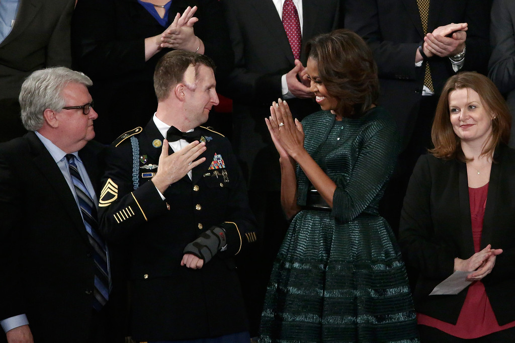 . WASHINGTON, DC - JANUARY 28:  First lady Michelle Obama (R) stands with US Army Ranger Sergeant First Class Cory Remsburg before U.S. President Barack Obama delivers the State of the Union address to a joint session of Congress in the House Chamber at the U.S. Capitol on January 28, 2014 in Washington, DC. In his fifth State of the Union address, Obama is expected to emphasize on healthcare, economic fairness and new initiatives designed to stimulate the U.S. economy with bipartisan cooperation.  (Photo by Win McNamee/Getty Images)