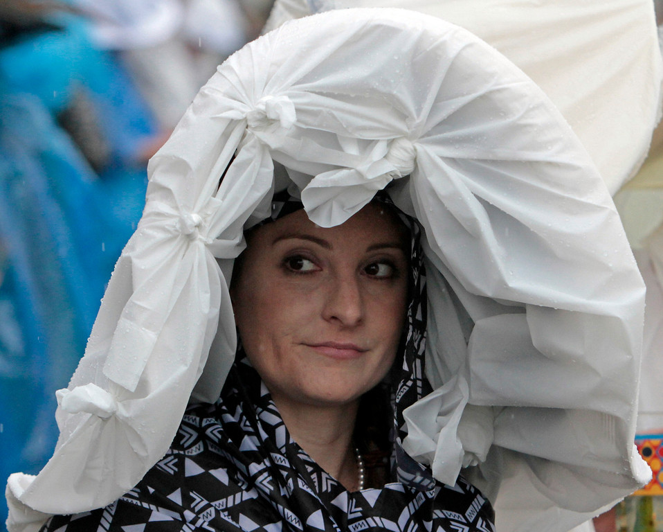 . Jennifer Parod, Tucson, Az., looks out from her plastic covered hat before the 139th Kentucky Derby at Churchill Downs Saturday, May 4, 2013, in Louisville, Ky. (AP Photo/Garry Jones)