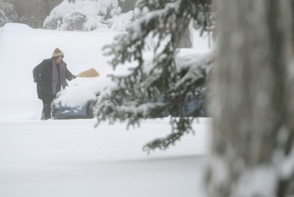 . DENVER, CO.- MARCH 23: A woman uses a broom to brush off the snow on her car. Snow arrived overnight in Denver and for much of Colorado with a foot or more expected in some areas of the foothills and eastern planes. (Photo By Kathryn Scott Osler/The Denver Post)