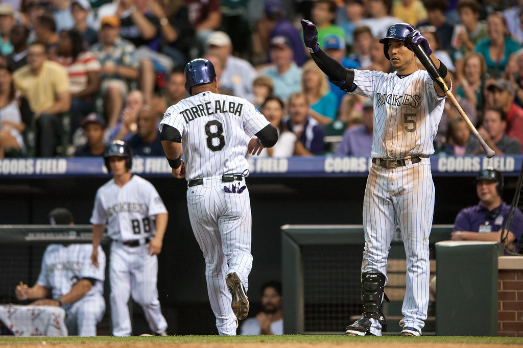 . DENVER, CO - JULY 24:  Yorvit Torrealba #8 of the Colorado Rockies crosses home plate for a run on a sacrifice by DJ LeMahieu #9 (not pictured) in the fifth inning as Carlos Gonzalez #5 signals that he doesn\'t need to slide during a game against the Miami Marlins at Coors Field on July 24, 2013 in Denver, Colorado. (Photo by Dustin Bradford/Getty Images)
