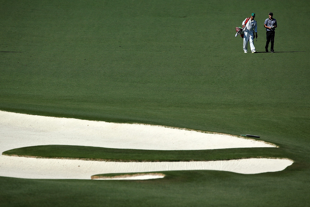 . Russell Henley of the United States waits on the tenth hole with his caddie Adam Hayes during the third round of the 2014 Masters Tournament at Augusta National Golf Club on April 12, 2014 in Augusta, Georgia.  (Photo by Andrew Redington/Getty Images)