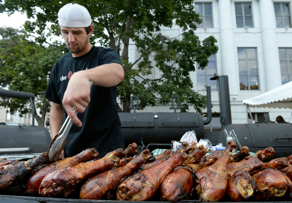. DENVER, CO - AUGUST 29: Austin Easterling tempts passers-by with a display of giant turkey legs. Hungry visitors make their way to the opening day of A Taste of Colorado at Civic Center Park in downtown Denver on Friday, Aug. 29, 2014. The food and music festival runs through Labor Day Weekend. (Kathryn Scott Osler/The Denver Post)