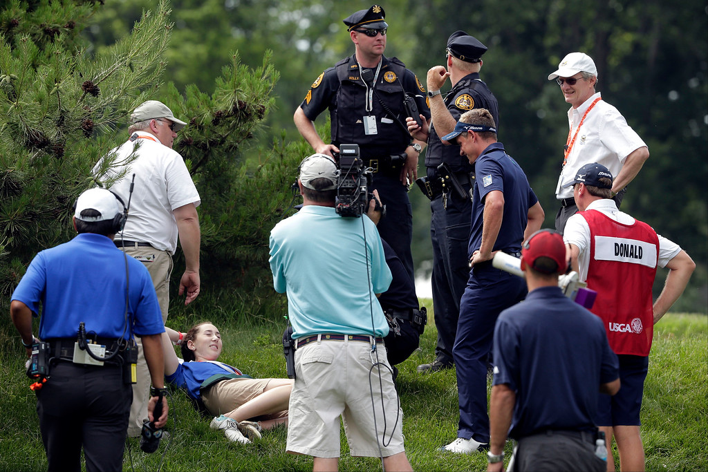 . Luke Donald, of England, fourth from right, checks on a course worker who was hit by his errant shot on the third hole during the fourth round of the U.S. Open golf tournament at Merion Golf Club, Sunday, June 16, 2013, in Ardmore, Pa. (AP Photo/Charlie Riedel)