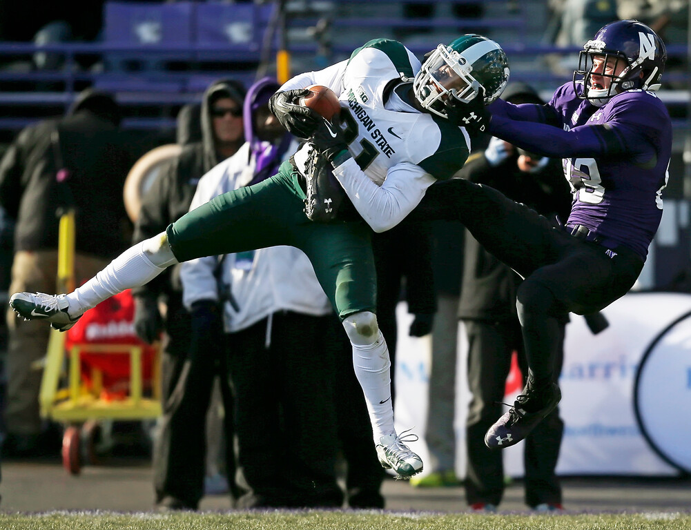 . In this Nov. 23, 2013, Michigan State cornerback Darqueze Dennard (31) intercepts a pass intended for Northwestern wide receiver Mike McHugh (83) during the second half of an NCAA football game in Evanston, Ill. Dennard was selected in the first round, 24th overall, by the Cincinnati Bengals in the NFL draft on Thursday, May 8, 2014. (AP Photo/Andrew A. Nelles, File)