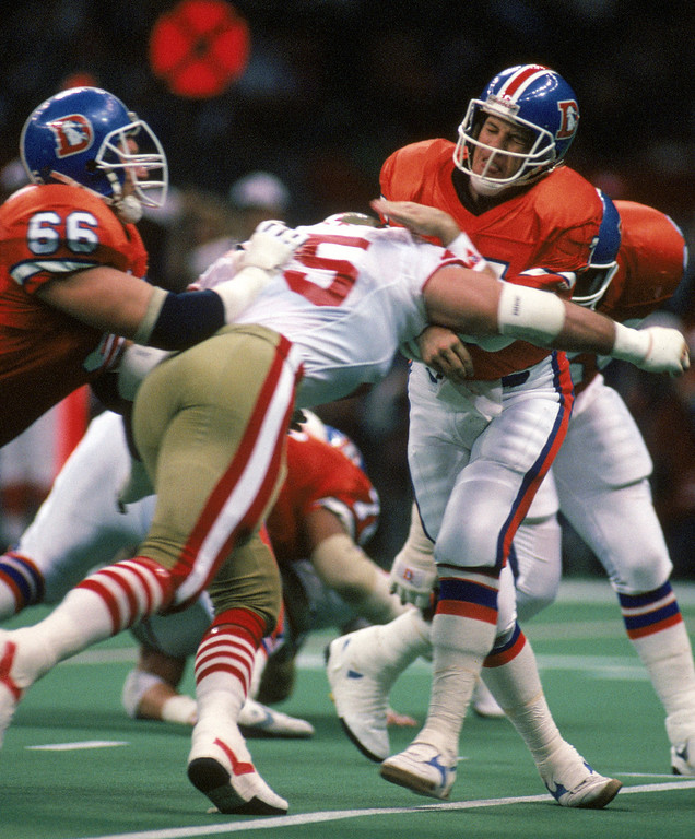 . Third and ten at the San Francisco 49ers twenty five yard line, Quarterback John Elway #7 of the Denver Broncos gets hit as he misses a pass intended for wide receiver Mark Jackson, the Broncos settle for a field goal during Super Bowl XXIV at the Louisiana Superdome on January 28, 1990 in New Orleans, Louisiana.    (Photo by George Rose/Getty Images)