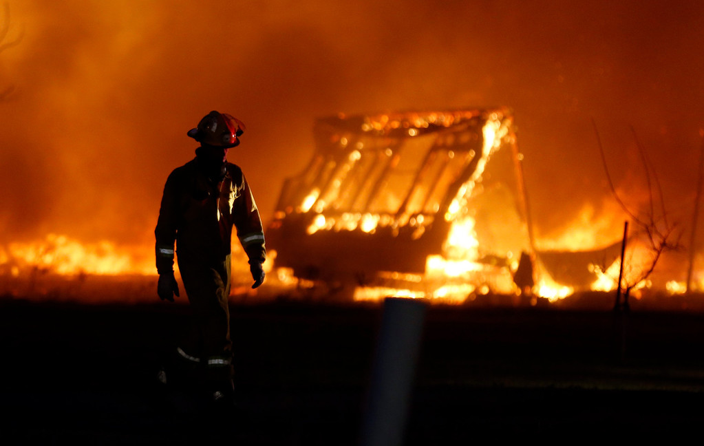 . A firefighter walks past a burning mobile home at a mobile home park near Prairie Grove Rd. and Douglas during Oklahoma wildfires in south Logan County, Sunday, May 4, 2014. Firefighters worked through the night and into early Monday to battle a large wildfire that destroyed at least six homes and left at least one person dead after a controlled burn spread out of control in central Oklahoma. (AP Photo/The Oklahoman, Nate Billings)