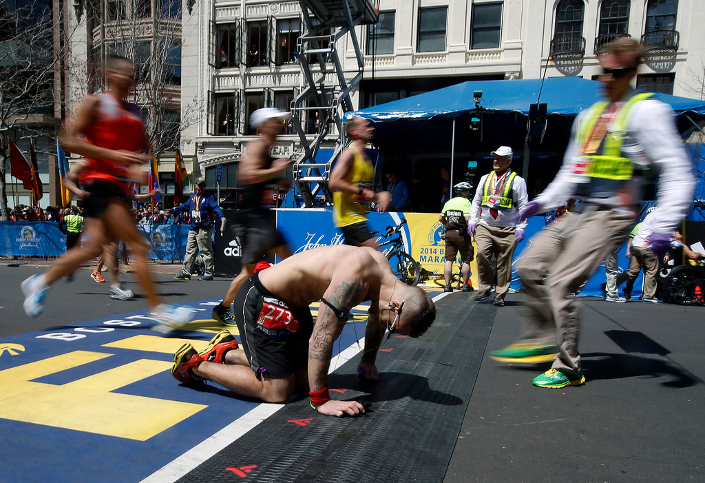 . Kyle Marshall, of Phoenix, collapses at the finish line of the 118th Boston Marathon Monday, April 21, 2014 in Boston. (AP Photo/Elise Amendola)