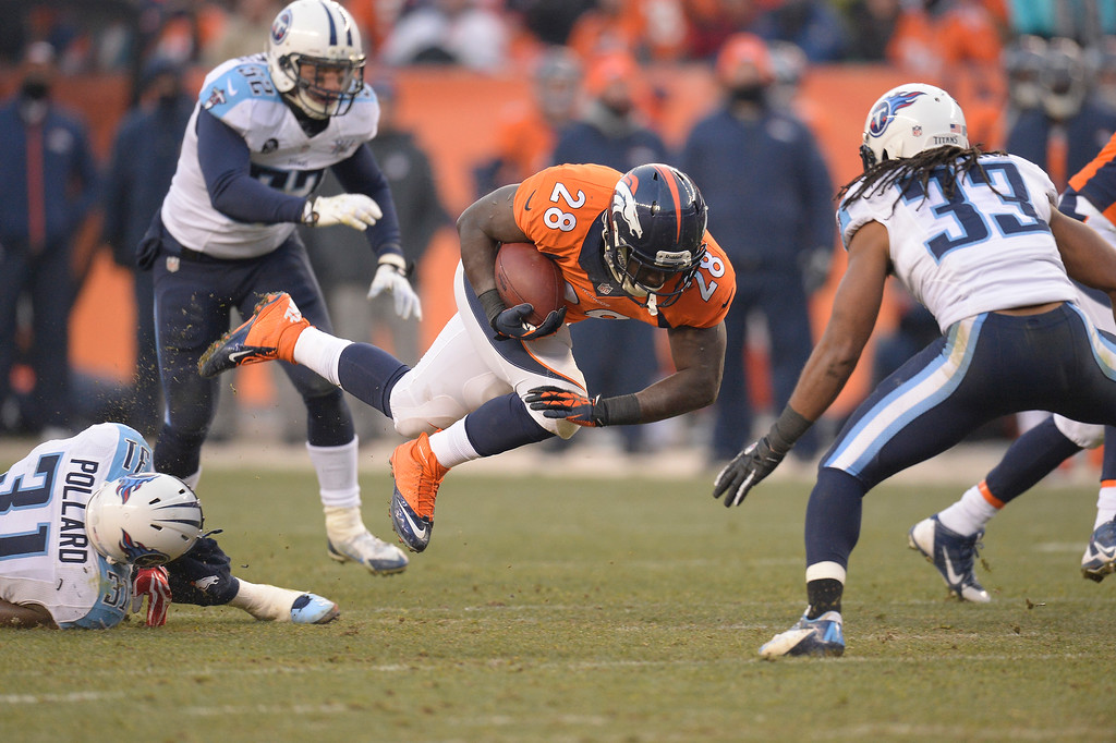 . Denver Broncos running back Montee Ball (28) is tripped up by Tennessee Titans strong safety Bernard Pollard (31) in the third quarter.  (Photo by John Leyba/The Denver Post)