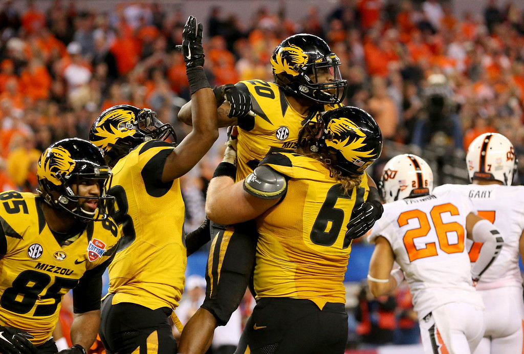 . ARLINGTON, TX - JANUARY 03:  Henry Josey #20 of the Missouri Tigers celebrates scoring a 25-yard touchdown with Max Copeland #61 in the fourth quarter against the Oklahoma State Cowboys during the AT&T Cotton Bowl on January 3, 2014 in Arlington, Texas.  (Photo by Ronald Martinez/Getty Images)